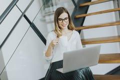 年轻女实业家用在办公室台阶的膝上型计算机饮用的咖啡 免版税库存图片