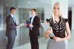 年轻女实业家画象在有同事的办公室在背景中 免版税库存图片