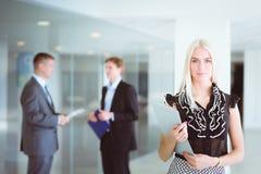 年轻女实业家画象在有同事的办公室在背景中 库存照片