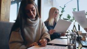 年轻女实业家自由职业者签署在咖啡馆的文件 股票录像