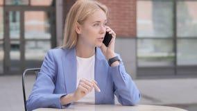 年轻女实业家谈话在电话坐室外