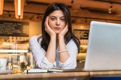 年轻女实业家,学生画象,在白色女衬衫穿戴了,坐在咖啡馆的桌上在计算机前面 库存照片