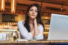 年轻女实业家,学生画象,在白色女衬衫穿戴了,坐在咖啡馆的桌上在计算机前面 免版税库存图片