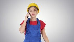 年轻女工谈话在电话,当走在梯度背景时 股票视频