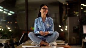年轻女性举行的膝上型计算机坐的莲花姿势,满意对被完成的工作,成功 免版税库存照片