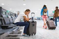年轻女性乘客在机场,使用她的片剂计算机 库存照片