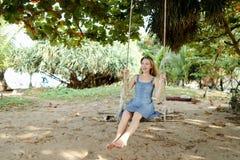 年轻女性佩带的牛仔裤在背景中穿戴和乘坐在摇摆,沙子 免版税库存图片
