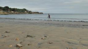 年轻女性单独在与北欧样式自然环境岩石和沙子的无人居住的狂放的大西洋海岸  影视素材