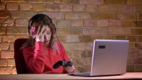 年轻女性博客作者画象打电子游戏使用控制杆和无法与耻辱的红色有冠乌鸦的bricken 影视素材