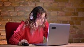 年轻女性博客作者画象红色有冠乌鸦的愉快地拍她的手和谈话使用膝上型计算机bricken墙壁 影视素材