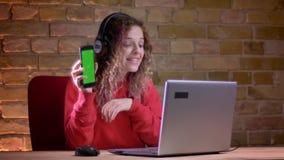 年轻女性博客作者画象红色有冠乌鸦的显示智能手机显示到膝上型计算机里bricken墙壁背景 股票录像