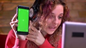年轻女性博客作者画象红色有冠乌鸦的显示智能手机绿色显示到膝上型计算机里bricken墙壁背景 影视素材