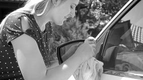 年轻女性司机清洁汽车边镜子黑白画象  免版税图库摄影