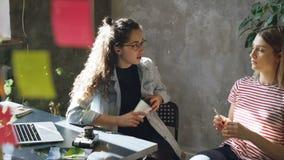 年轻女性同事坐在分享想法的书桌在现代办公室 与五颜六色的备忘录的Glassboard 股票录像