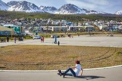 年轻女性四轮溜冰者在地面上跌倒了在学校运动场 图库摄影