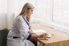 年轻女性在医生` s室文字的医生运转的书桌 库存图片