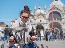 年轻女性在圣马可广场的旅客坐的和哺养的鸽子 库存照片