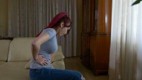 年轻女性在应付胃病症的严厉stomachache结果的痛苦中在家坐长沙发 影视素材