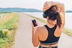 年轻女性开始的跑步和听到音乐使用智能手机和无线耳机 库存图片