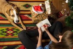 年轻女性得出在贺卡的一个滑稽的假日棍子形象并且写祝贺愉快的圣诞节假日 免版税图库摄影