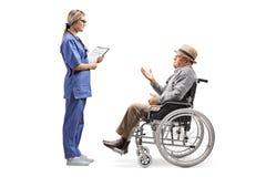 年轻女性护士谈话与轮椅的一个年长绅士 免版税图库摄影