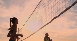 年轻女性排球运动员传和钉牢球在网在一个晴朗的夏天晚上 适合的白种人女孩 股票录像