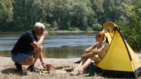 年轻女性旅客在帐篷坐 女孩通过人一杯茶 人喝茶和笑 股票视频