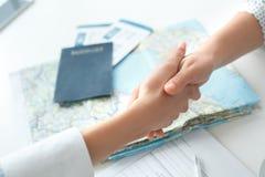年轻女性旅行代理人顾问在与顾客握手的游览机构中 免版税库存图片