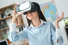 年轻女性旅行代理人顾问在演奏虚拟现实耳机的游览机构中 免版税库存图片