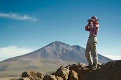 年轻女性旅行家在山使用双筒望远镜 免版税库存照片