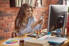 年轻女性有在家运转的长发的或在顶楼样式办公室 聊天通过智能手机和微笑的她 设计师,编辑, 免版税图库摄影