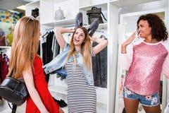 年轻女性朋友获得乐趣,当购物在服装店时 使用她的鞋子的俏丽的女孩显示滑稽的兔宝宝耳朵 图库摄影