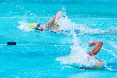 年轻女性游泳者在自由式冲程赛跑在学校swimm 免版税库存图片