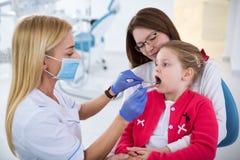 年轻女性牙医看女孩牙 库存图片