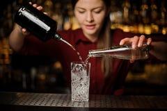年轻女性男服务员poting的杜松子酒和甜糖浆到玻璃里 免版税库存照片