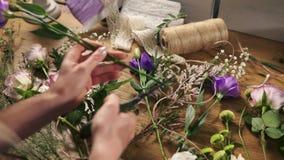 年轻女性白肤金发的卖花人花为花束做准备 工作在她花店做的花店所有者的手 股票录像
