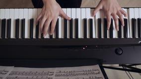 年轻女性的弹大平台钢琴的钢琴演奏家手 股票录像