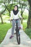 年轻女性穆斯林骑自行车 免版税库存图片