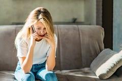年轻女性穿戴了担心和偶然不快乐的神色,当谈话在手机时 库存图片