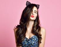 年轻女性给亲吻显示红色嘴唇与组成佩带减速火箭的样式猫耳朵现代桃红色背景画报女孩 库存图片