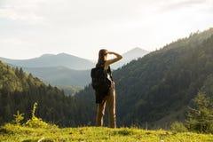 年轻女性背包徒步旅行者站立小山的上面在日落 免版税库存照片
