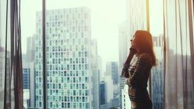 年轻女性自由职业者或商人谈话在电话由在豪华公寓的全景窗口在事务 股票视频