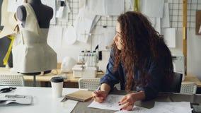 年轻女性艺术家时装设计师画妇女` s服装剪影在桌上在现代演播室 时装模特,缝合 股票录像