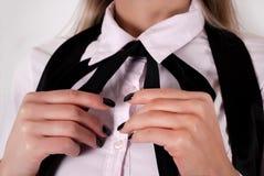 年轻女性藏品领带在脖子上用有黑指甲油的手 免版税库存照片