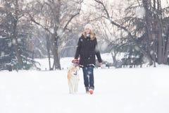 年轻女性走在多雪的天机智她的日本秋田宠物 Wi 免版税图库摄影
