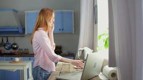 年轻女性身分在厨房里谈话在手机 股票录像