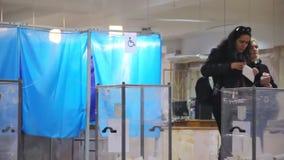 年轻女性选民在投票箱投入选票 乌克兰总统的竞选 从另外政党monito的观察员 股票录像
