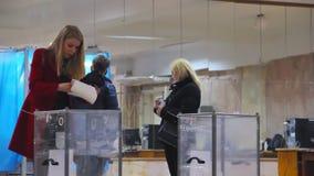 年轻女性选民在投票箱投入选票 r 从另外政党monito的观察员 股票视频