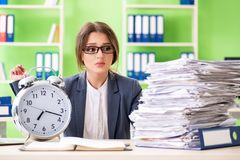 年轻女性雇员非常繁忙与持续的文书工作及时m 图库摄影