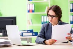 年轻女性雇员非常繁忙与持续的文书工作 免版税库存图片